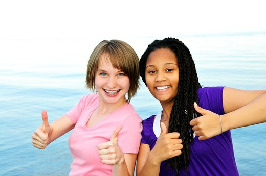 Portrait of two teenage girl friends showing thumbs up : Stock Photo
