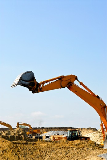 Yellow bulldozer machines digging and moving earth at construction site : Stock Photo