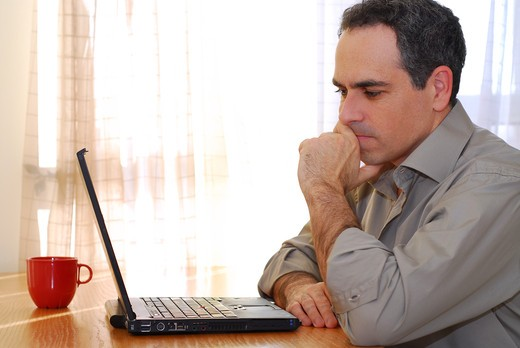 Man sitting at a desk and looking into his computer : Stock Photo