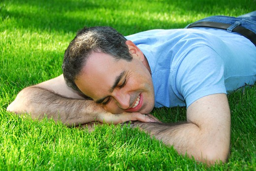 Stock Photo: 4183R-7436 Attractive man lying on green grass in a park relaxing