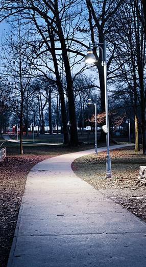 Path through city park at dusk with street lamps : Stock Photo
