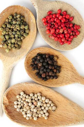 Stock Photo: 4183R-8324 Four kinds of peppercorns in wooden cooking spoons