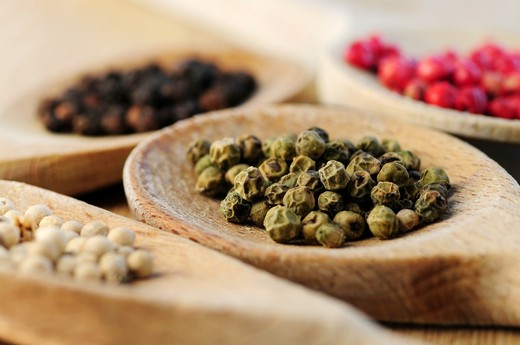 Four kinds of peppercorns in wooden cooking spoons, macro : Stock Photo
