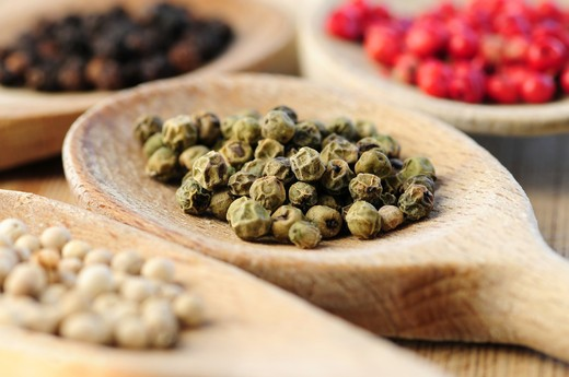 Stock Photo: 4183R-8327 Four kinds of peppercorns in wooden cooking spoons macro