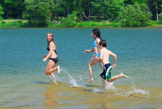 Group of children running into clear lake water : Stock Photo