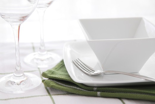 Place setting with white dishes and wine glasses : Stock Photo
