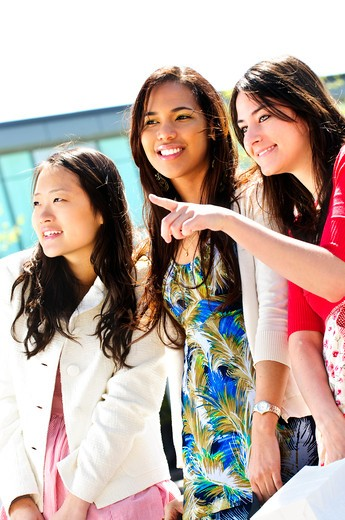 Stock Photo: 4183R-9108 Three young girlfriends at outdoor mall pointing