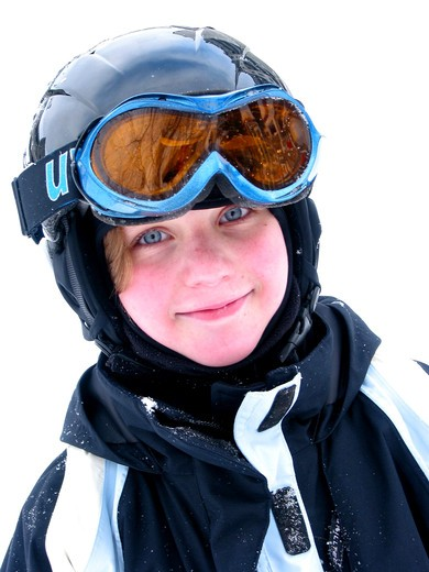 Stock Photo: 4183R-9142 Cute young girl wearing ski helmet and goggles smiles after a day of skiing