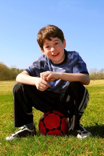 Young cute happy boy sitting on a red soccer ball outside : Stock Photo