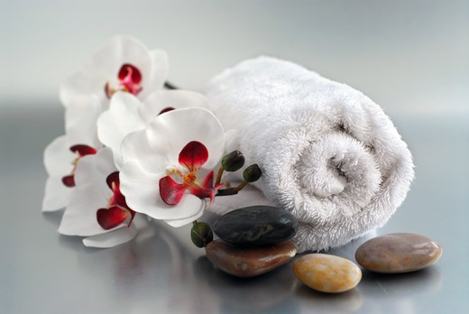 White rolled up towel with massage stones and an orchid : Stock Photo