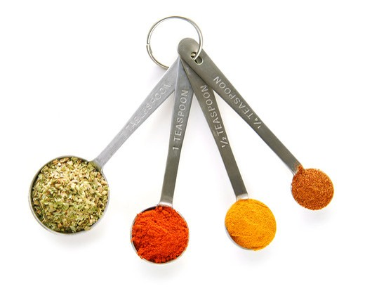 Assorted spices in measuring spoons on white background : Stock Photo
