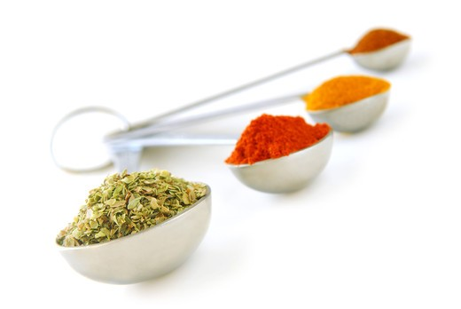 Assorted spices in metal measuring spoons on white background : Stock Photo