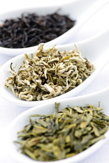 Black, white and green dry tea leaves in spoons : Stock Photo
