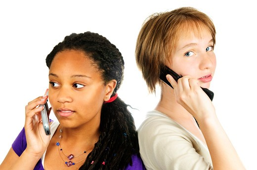 Isolated portrait of two teenage girls with cell phones : Stock Photo