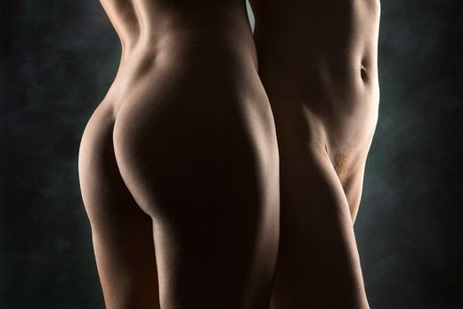 Hips and buttocks of nude Hispanic and Caucasian women standing together. : Stock Photo