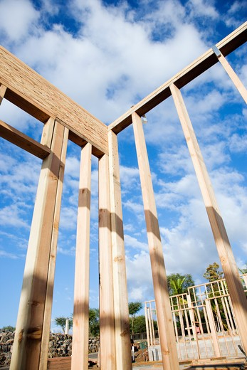 Section of a construction wall framed out in wood against a blue sky. Another framed building can be seen in the background. Vertical shot. : Stock Photo