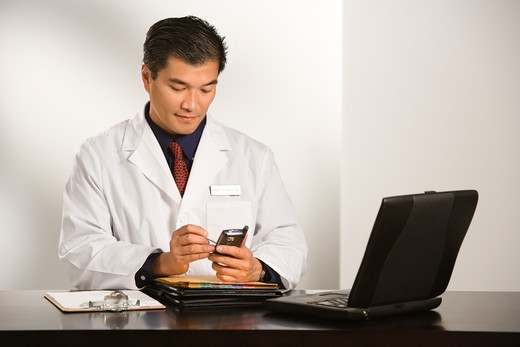 Asian American male doctor sitting at desk with charts and laptop computer using pda. : Stock Photo