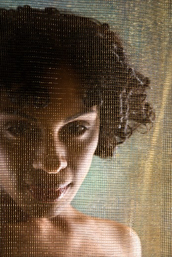 Nude Hispanic woman looking at viewer from behind sheer fabric. : Stock Photo