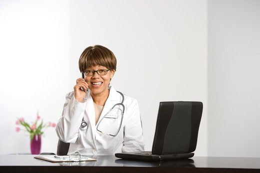 Stock Photo: 4184R-10231 African American middle-aged female doctor sitting at desk working on laptop, talking on cell phone, smiling and looking at viewer.