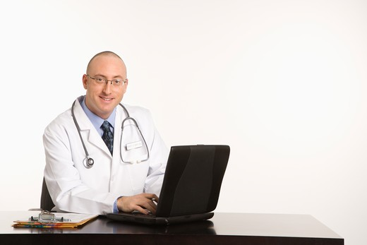 Caucasian mid adult male physician sitting at desk with laptop computer. : Stock Photo