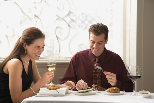 Stock Photo: 4184R-10487 Mid adult Caucasian couple dining in restaurant and laughing.