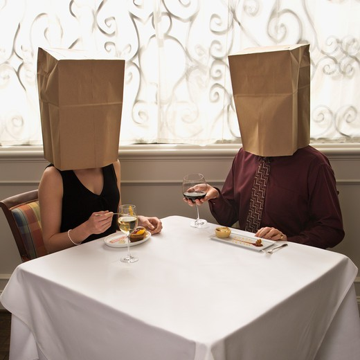 Mid adult Caucasian couple dining in a restaurant with paper bags over heads. : Stock Photo