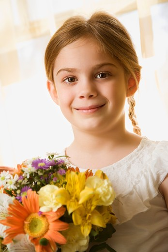 Caucasian girl smiling at viewer with bouquet of flowers. : Stock Photo