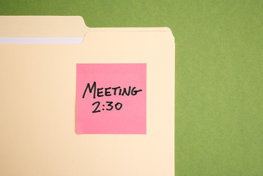 Folder with pink sticky note reminder for a meeting on a green background. : Stock Photo