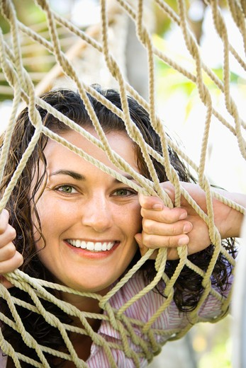 Stock Photo: 4184R-11011 Portrait of pretty young adult Caucasian brunette female peeking through hammock weave and smiling at viewer.