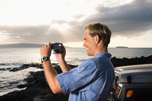 Side view of a smiling Caucasian man photographing a scenic sunset at a beach. Horizontal format. : Stock Photo