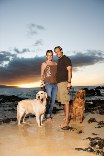 A man and woman smile at the camera as they hold the leashes of their dogs on a beach. Vertical format. : Stock Photo