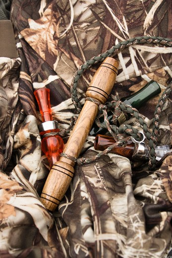 Stock Photo: 4184R-11336 Still life shot of bird calls against camouflage clothing.