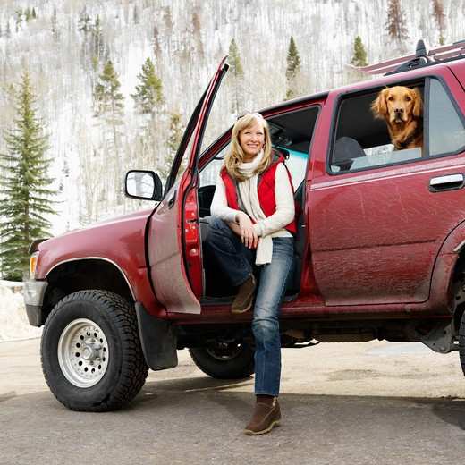 Stock Photo: 4184R-11590 Woman sitting in dirt splattered SUV with door open as dog in back seat looks out open window in snowy countryside.