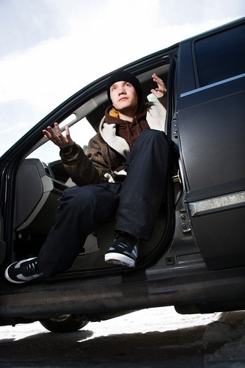 Stock Photo: 4184R-11671 Caucasian male teenager sitting in car making hand gesture.