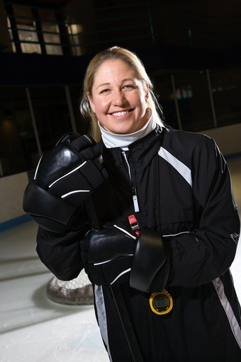 Female hockey coach in uniform standing smiling. : Stock Photo