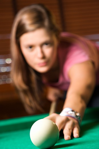 Young woman concentrating while shooting pool. Vertical shot. : Stock Photo