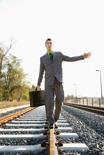 Young businessman with a briefcase balances on railroad tracks. Vertical shot. : Stock Photo