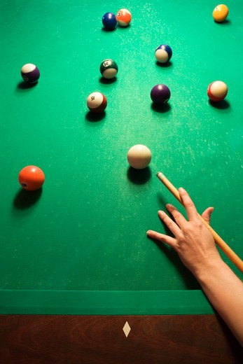 Stock Photo: 4184R-1228 Woman's hand preparing to hit pool ball while playing billiards.