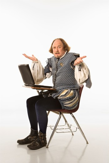William Shakespeare in period clothing sitting in school desk with laptop and shrugging at viewer. : Stock Photo