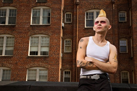 Portrait of a mid-adult Caucasian male punk  with building in background. : Stock Photo