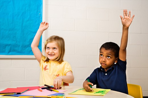 Boy and Girl raising hands in art class. Horizontally framed shot. : Stock Photo