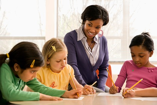Stock Photo: 4184R-12382 Teacher helping students in school classroom. Horizontally framed shot.