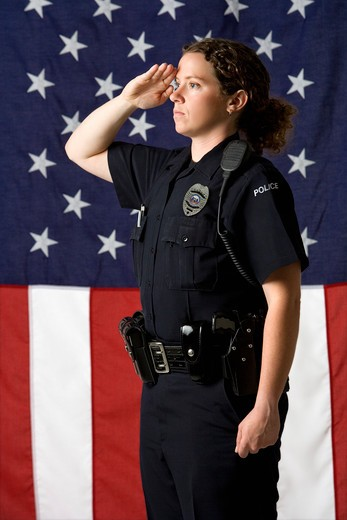 Portrait of mid adult Caucasian policewoman saluting with American flag as backdrop. : Stock Photo
