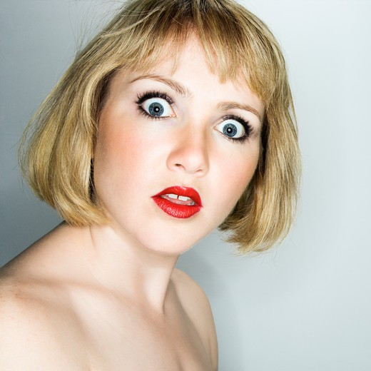 Stock Photo: 4184R-12578 Portrait of young blonde caucasian woman who is looking at the viewer with confused expression.