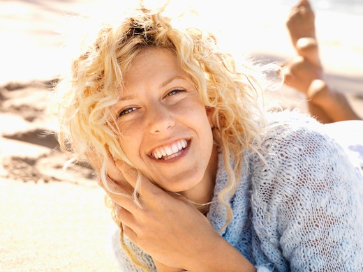 Stock Photo: 4184R-12620 Close up portrait of attractive young woman lying in sand on Maui, Hawaii beach smiling.