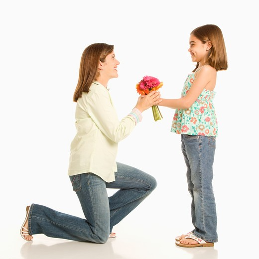 Daughter giving bouquet of flowers to mother. : Stock Photo