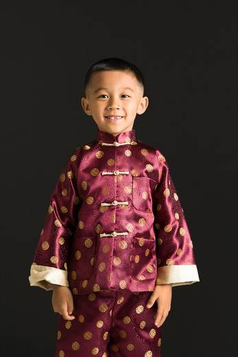 Stock Photo: 4184R-12953 Asian boy in traditional attire standing against black background.