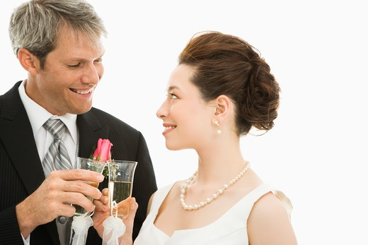 Stock Photo: 4184R-13045 Caucasian groom and Asian bride toasting with champagne glasses.