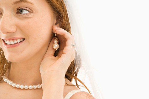 Stock Photo: 4184R-13101 Caucasian bride adjusting her earring.
