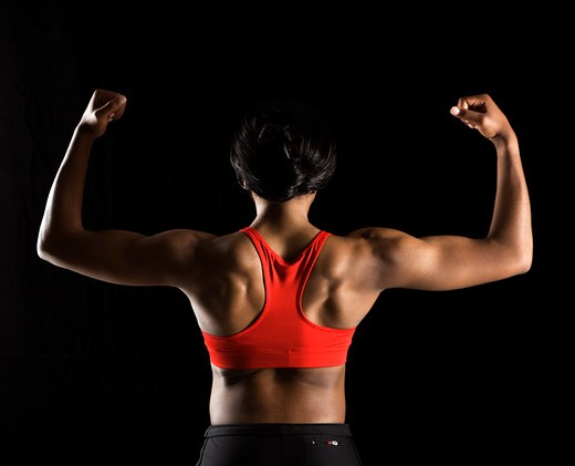 Back of muscular African American woman with biceps flexed. : Stock Photo
